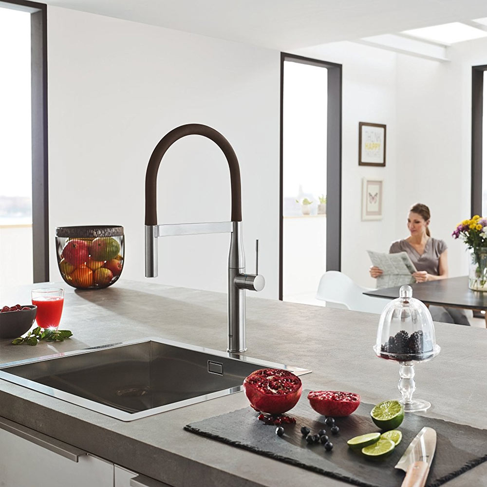GROHE Essence Professional Kitchen Sink Mixer - SuperSteel - positioned on a stylish kitchen worktop with a chic sink - surrounded by fresh fruits.