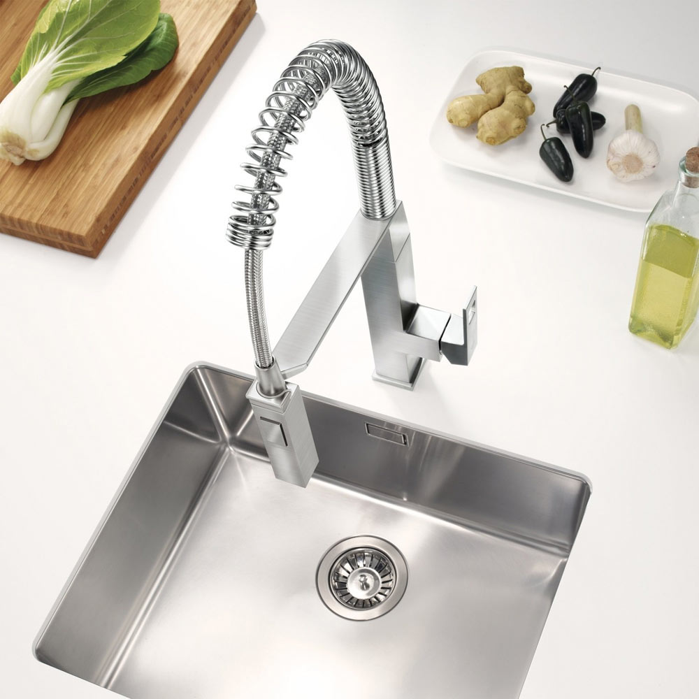 GROHE Eurocube Professional Kitchen Sink Mixer - SuperSteel - Intalled on to a white kitchen worktop with a stanless steel sink. Fresh vegetables accompany the image such as leeks, ginger and garlic.
