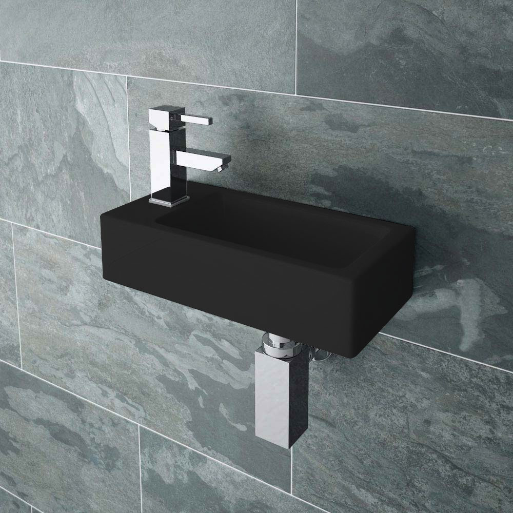 Rondo Black Wall Hung Small Cloakroom Basin - BLKVES047 - Close up image of a modern wall hung cloakroom basin in black set against grey tiles.