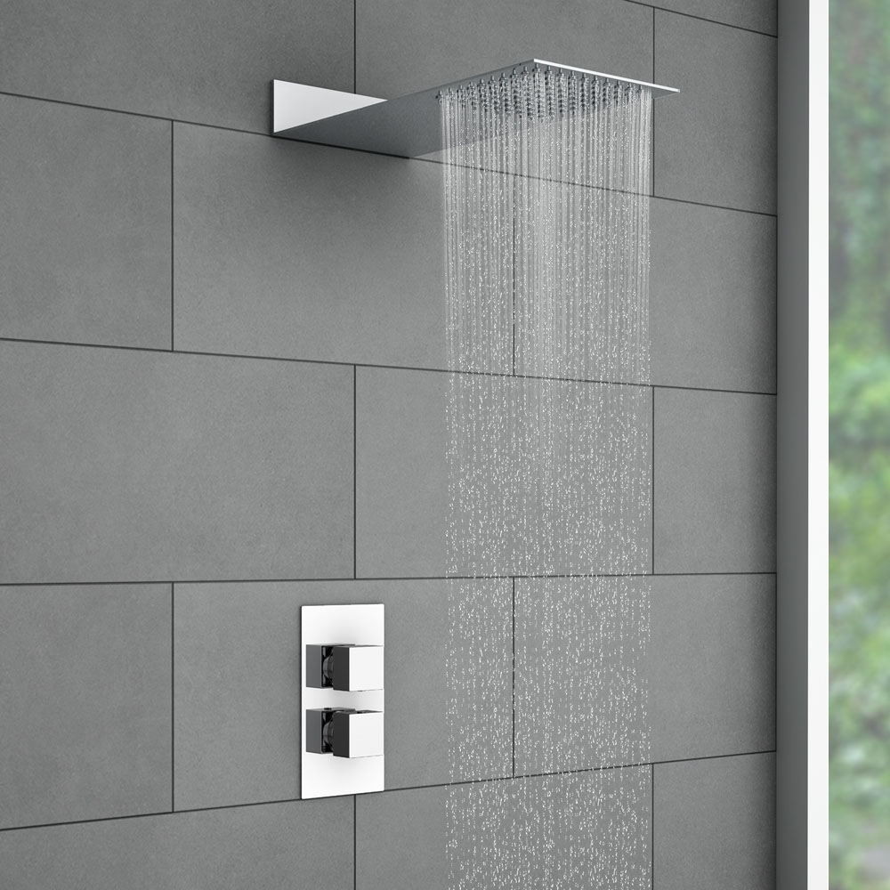 Milan Square Shower Package with Concealed Valve + Flat Fixed Shower Head - Close up image of a flat fixed shower head against grey tiles