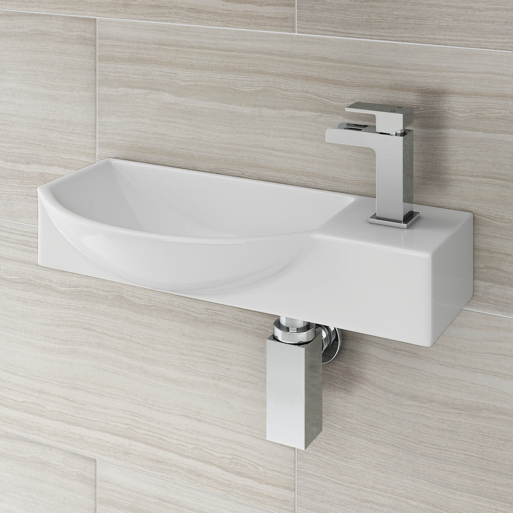 Valencia Mini Wall Hung Ceramic Basin - VWHB02 - Close up image of chrome basin tap on a wall hung rectangular cloakroom basin set against cream bathroom tiles.