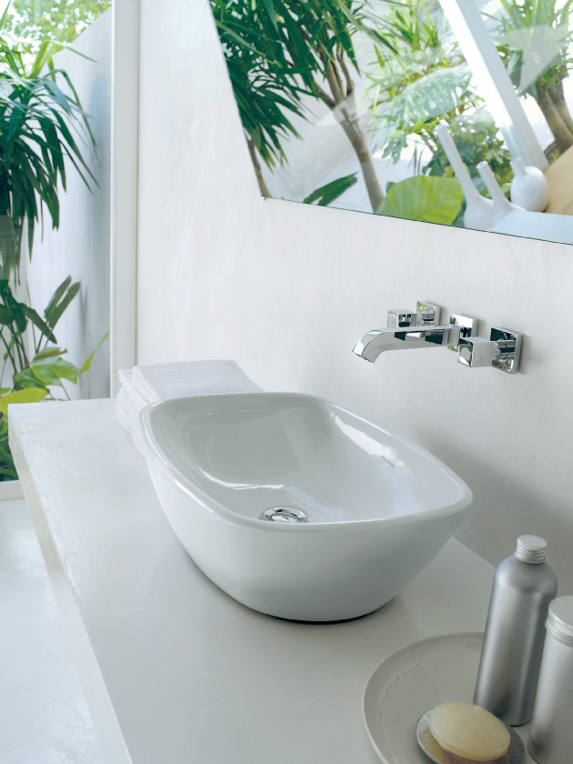 The greenery aside a counter top basin and wall mounted tap