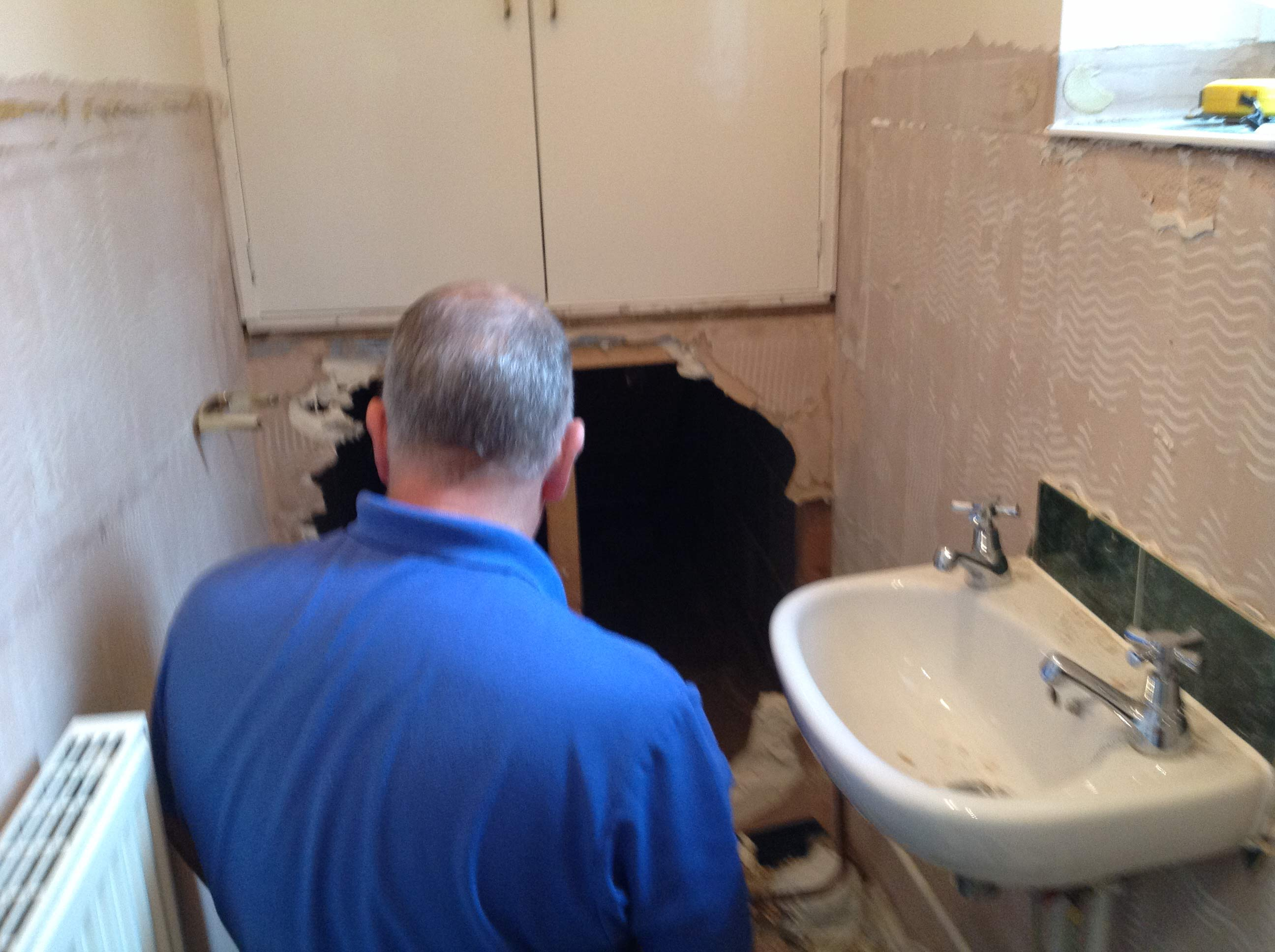 Tracey's husband Steve knocking through a wall during the installation of the new bathroom | Tracey's Under Stairs Bathroom - Barnoldswick, Lancashire